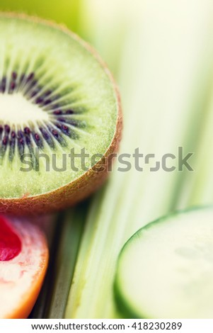diet, vegetable food, healthy eating and objects concept - close up of ripe kiwi and cucumber slices - stock photo