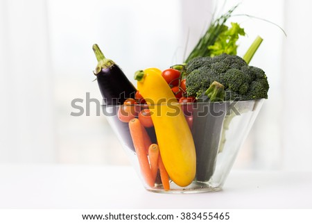 diet, vegetable food, healthy eating and objects concept - close up of ripe vegetables in glass bowl on table - stock photo