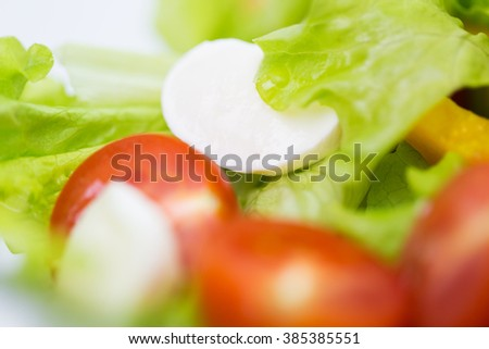 diet, vegetable food, healthy eating and objects concept - close up of vegetable salad with mozzarella cheese - stock photo