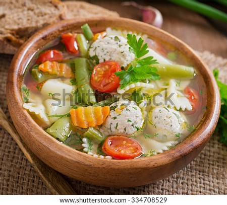Diet vegetable soup with chicken meatballs and fresh herbs in bowl.  - stock photo