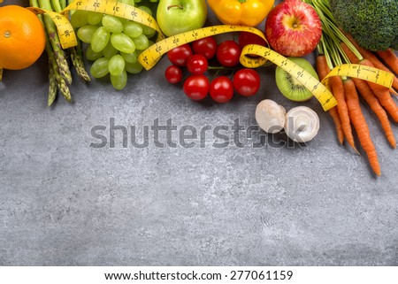 Diet weight loss breakfast concept with tape measure, organic vegetables and fruits. - stock photo
