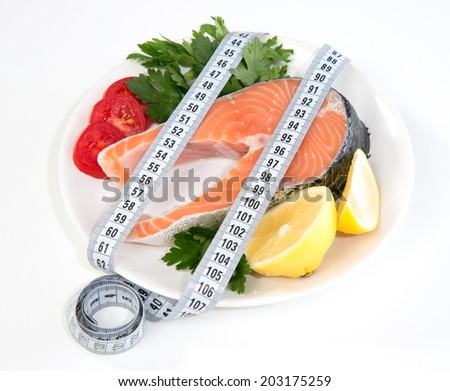 Diet weight loss concept. Fresh salmon steak for lunch with tape measure centimetr lemon tomatoes on a white background - stock photo