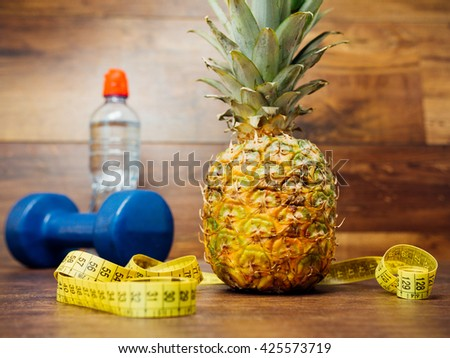 Diet weight loss fitness health care concept with measure tape, pineapple, water bottle, fitness dumbbell. Pineapple, metric ribbon on wood background. Diet heathy fitness sport lifestyle. - stock photo
