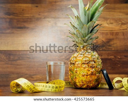 Diet weight loss fitness health care concept with measure tape, pineapple, water glass, fitness tracker bracelet. Pineapple, metric ribbon, smart gadget on wood background. Diet heathy lifestyle. - stock photo