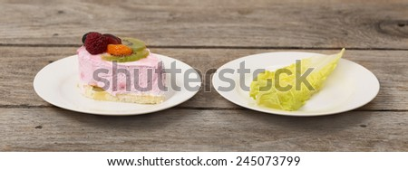 Diet, weight loss, low calories food concept - choice between pleasure and healthy lifestyle - plates with delicious sweet cake and single green salad leaf on the wooden table - stock photo