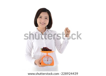 Diet woman holding grapes and scales on white background - stock photo