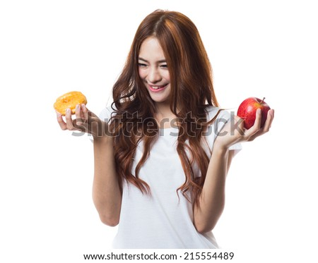 Diet young woman, choosing between donut and apple on white background