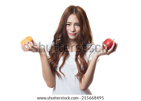 Diet young woman, choosing between donut and apple on white background - stock photo