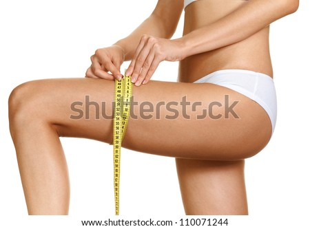 Diet - young woman is measuring her thigh with measuring tape