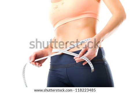 Diet - young woman is measuring her waist with measuring tape
