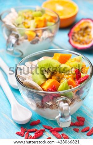 Dietary breakfast. Muesli, yoghurt, goji berries, tropical fruits: mango, kiwi, pineapple, passion fruit in cup on a blue background - stock photo