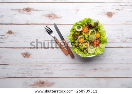 Dietary food background: vegetable salad with cucumber, cherry tomatoes on old wooden board, vegan cuisine - stock photo