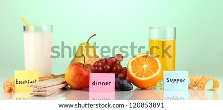 Dietary foods for breakfast, dinner and supper on green background
