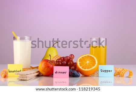 Dietary foods for breakfast, dinner and supper on purple background