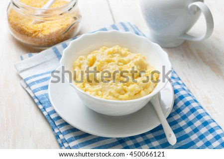 Dietary healthy breakfast. White cup with corn porridge on a blue napkin - stock photo