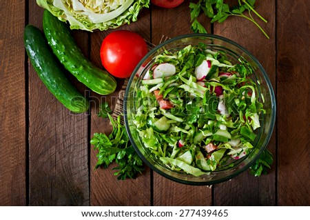 Dietary healthy salad of fresh vegetables in a glass bowl on a wooden background. Top view - stock photo