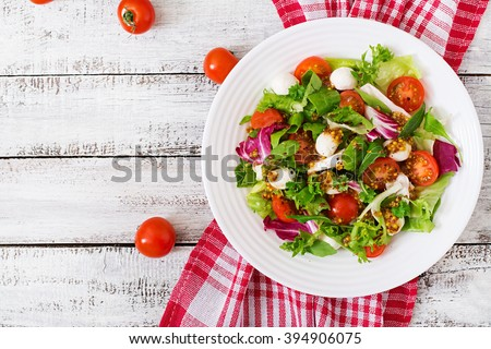 Dietary salad with tomatoes, mozzarella lettuce with honey-mustard dressing. Top view - stock photo