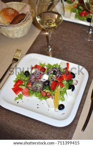 Dietary salad with vegetables, olives and cheese in the restaurant, table setting with a glass of wine, cozy and beautiful, restaurant menu