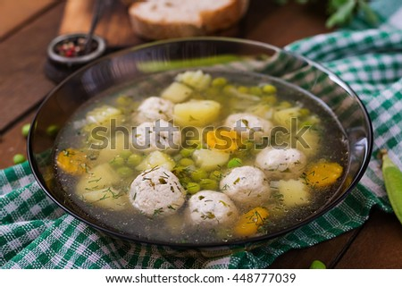 Dietary soup with chicken meatballs and green peas in a glass bowl on a wooden background.  - stock photo