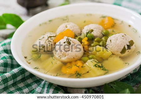 Dietary soup with chicken meatballs and green peas in a white bowl on a wooden background. - stock photo
