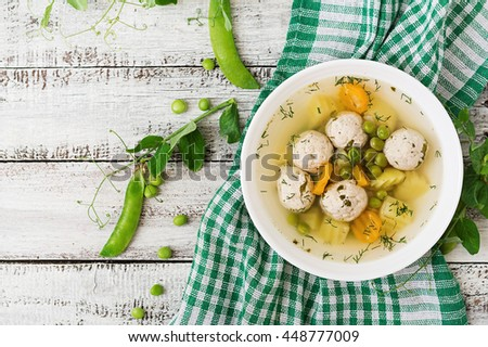 Dietary soup with chicken meatballs and green peas in a white bowl on a wooden background. Top view - stock photo