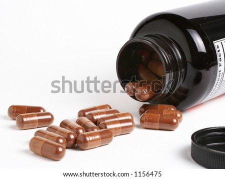 Dietary supplements flowing from a container - stock photo