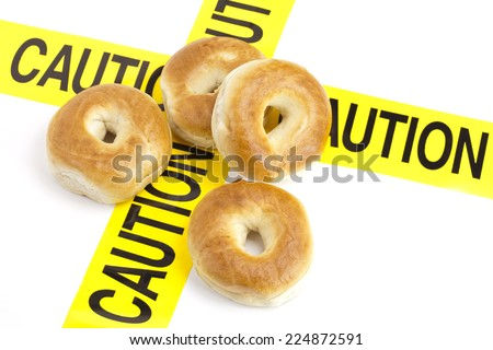 Dietary warning or gluten/wheat allergy warning (Fresh Bagels on top of the yellow caution tape)  - stock photo
