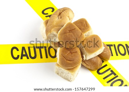 Dietary warning or gluten/wheat allergy warning ( Fresh baked bread rolls on top of the yellow caution tape) - stock photo