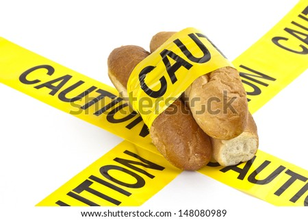 Dietary warning or gluten/wheat allergy warning (Slices of fresh French bread wrapped in yellow caution tape) - stock photo
