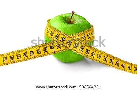 Dieting concept. Green apple with yellow measuring tape isolated on white