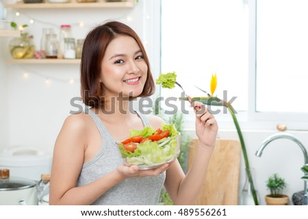 Dieting concept. Healthy Food. Beautiful Young Asian Woman eating fresh vegetable salad. Loosing Weight concept