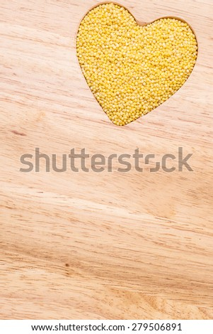 Dieting concept. Millet groats heart shaped on wooden surface. Healthy food help lower cholesterol. - stock photo