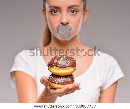 Dieting concept: pretty young woman with chocolate cake and closed mouth by sticky tape. - stock photo