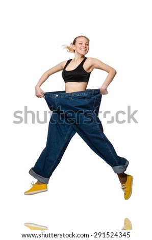 Dieting concept with big jeans on white - stock photo
