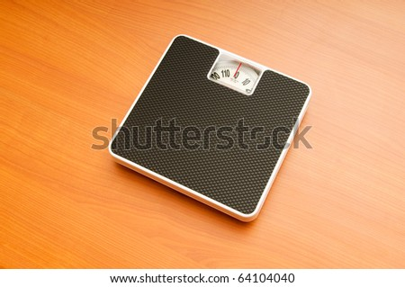 Dieting concept with scales on the wooden floor - stock photo