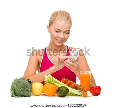 dieting, food, healthcare and technology concept - smiling sporty woman with fruits and vegetables counting calories in smartphone - stock photo