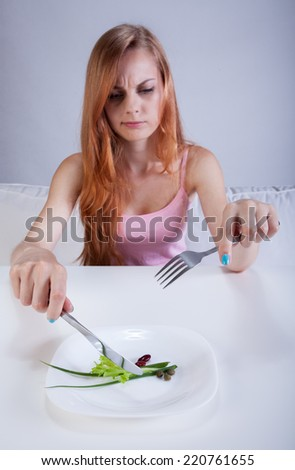 Dieting girl eating a little greens for lunch - stock photo