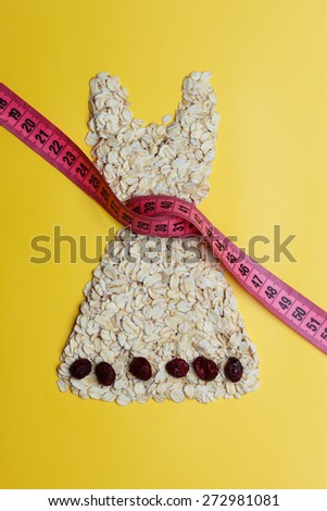 Dieting healthy eating slim down concept. Female dress shape made from oatmeal dried fruit with measuring tape around thin waist on yellow - stock photo