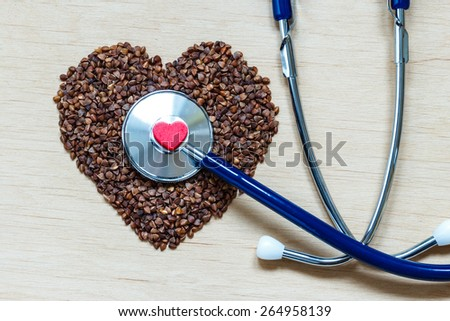 Dieting healthy living concept. Buckwheat groats heart shaped and stethoscope on wooden surface.. Healthy food good for cardiovascular system - stock photo
