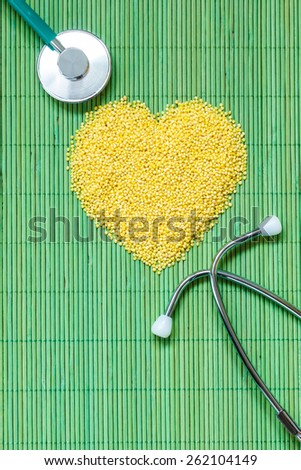 Dieting healthy living concept. Millet groats heart shaped and stethoscope on green mat surface.. Healthy food help lower cholesterol. - stock photo
