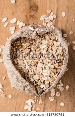 Dieting. Oat cereal in burlap sack on wooden surface, top, view. Healthy food for lowering cholesterol, protect heart. - stock photo