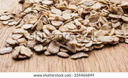 Dieting. Oat cereal on wooden surface. Healthy food for lowering cholesterol, protect heart. - stock photo