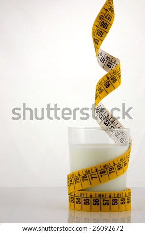 Dieting on low fat food (milk). A glass of low fat milk, surrounded by a coloured measuring tape, hanging  from above - stock photo