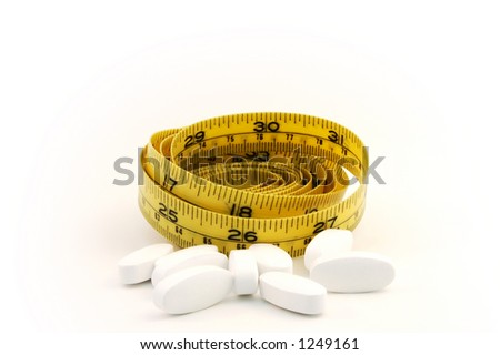 Dieting pill concept with yellow measure tape - stock photo