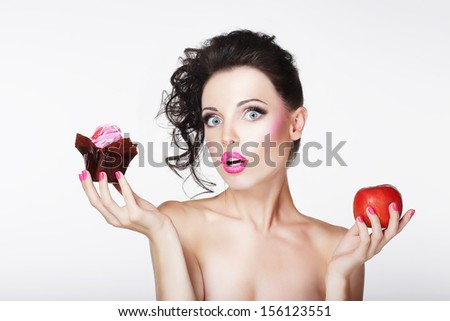 Dieting. Unsure Bewildered Girl Choosing Apple or Cake - stock photo
