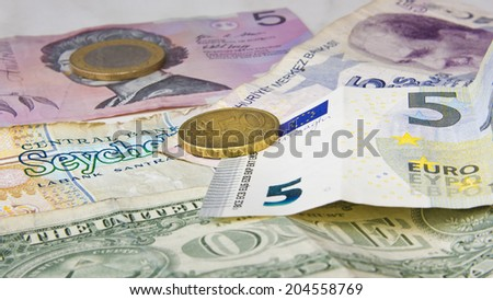 Different banknotes and coins from Europe, USA, Seychelles, Australia and Turkey. - stock photo