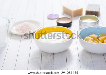 different bath salts, bees wax , makeup base, soaps and cosmetic creams on white wooden background
