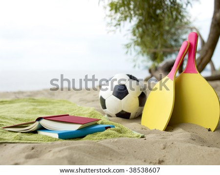 Different beach games lying in the sand. - stock photo