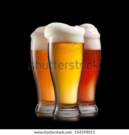 Different beer in glasses isolated on black background - stock photo