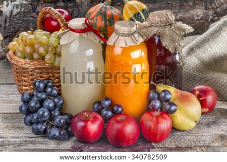 Different bottles of fresh juice with ripe fruits and vegetables on rustic table and in front of wood  - stock photo